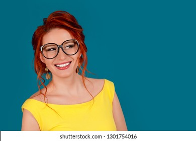 Smile. Close up portrait head shot cute gorgeous beautiful charming young happy woman, student smiling, laughing looking to side on blue background wall. Positive emotion facial expression feeling