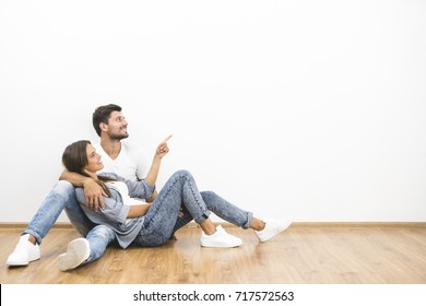 The smile couple sit and gesture on the background of the white wall