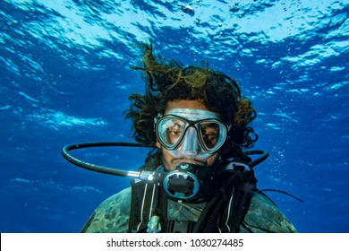 Smile of crazy Scuba diver underwater selfie in the deep blue ocean and backlight sun