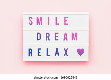 SMILE DREAM RELAX written in light box on pink background. Healthcare concept. Motivation quote. Top view.