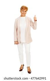 Smile elegant senior woman showing thumb up