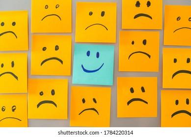 smile face sticky note surrounded by sad face stickynote