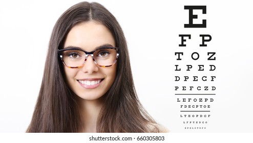 smile female face with spectacles on eyesight test chart background, eye examination ophthalmology concept
