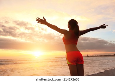 Smile Freedom and carefree sport woman on beach. She is enjoying serene ocean nature during sport outdoors. asian beauty