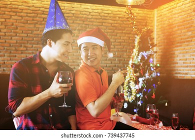 Smile Gay men couple with santa hats looking each other and celebrating Christmas party. Xmas celebration with wine or champagne drink, balloons, X'mas tree. One guy wanna go outside to private room.
