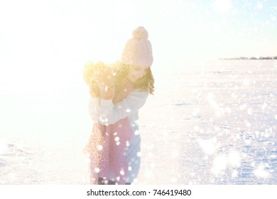 Smile girl in a pink hat, mittens and scarf throws snow on winter field. Beauty girl in hat and scarf.