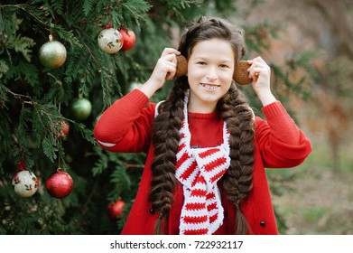 Smile girl waiting for a Christmas in the wood. Christmas in juli. Half-length portrait of a girl in red sweater near the christmas tree and holding decoration