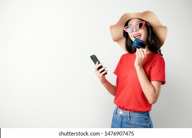 Smile happily Asian woman red t-shirt holding smartphone and credit card shopping online on white background.