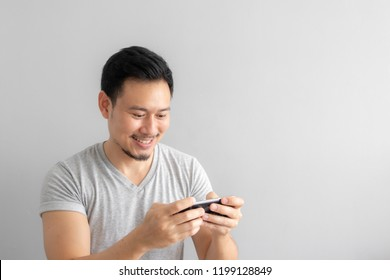 Smile and happy face of Asian man play mobile game.