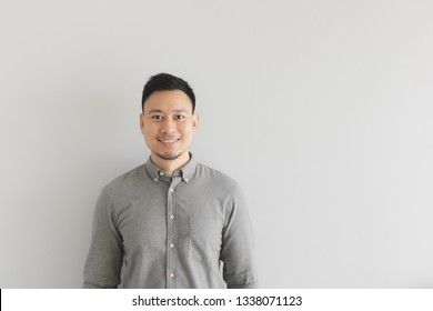 Smile happy face of ordinary Asian man in grey shirt. Concept of charming and positive thinking.