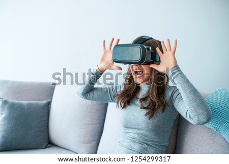 f5f678cce7f2 Smile happy woman getting experience using VR headset glasses of virtual  reality at home much gesticulating
