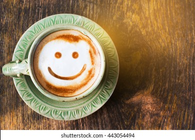 Smile of latte coffee with sunshine on wooden background.(Top view)