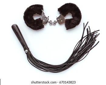A smile made from sex toys. Furry Handcuffs and Leather whip.