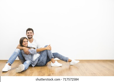 The smile man and woman sit on the background of the empty wall