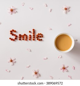 """""""Smile"""" message made of red berries with cup of coffee or tea and flowers"""