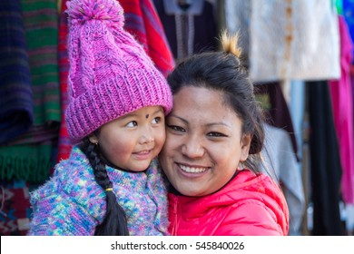 The smile of mother and daughter is beautiful. mom and kid happily pose for photo in Mahakal market ,Darjeeling,India (30,12,16)