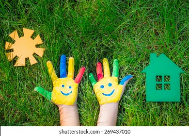 Smile on hands, paper house and sun on green grass. Children having fun in spring outdoors. Ecology concept