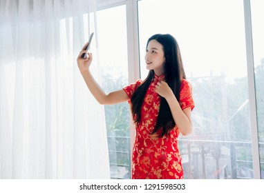 Smile of Portrait Beauty Asian Woman with Chinese dress,Qipao,Cheongsam Chinese New Year Using Smartphone Technology Selfie near Window in Clean White Room.