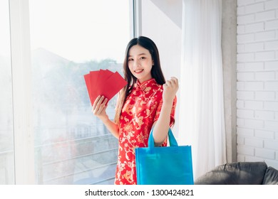 Smile of Portrait Beauty Asian Woman with Chinese dress,Qipao,Cheongsam Chinese New Year her hold Red envelope,Shopping Bag near Window in Clean White Room.