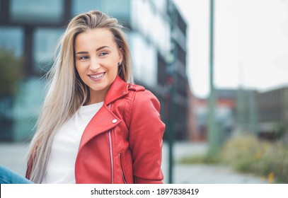 Smile portrait of a young woman looking to side. Outdoors daylight. Half length of cute girl wearing casual clothing. Outside
