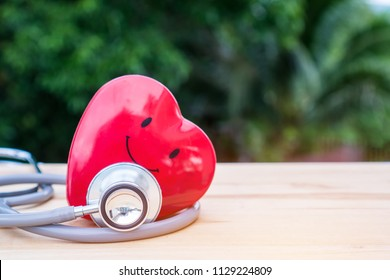 Smile Red heart with stethoscope on  wood desk at outside hospital. Concept of Health care insurance and medicals service for good life