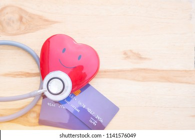 Smile Red heart stethoscope on Mock up Credit Card with cardholder in hospital wood desk. Concept of Health insurance cost of care, self-care during illness using payments card for medicals service.
