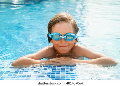 A smile seven years old kid with goggles in swimming pool