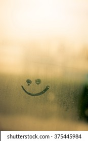 Smile sign on foggy window background. Happy sunny face
