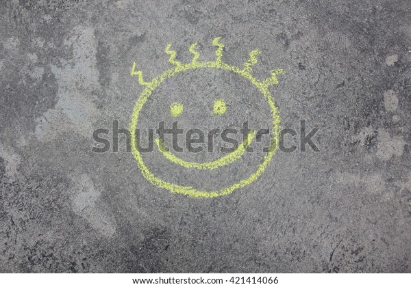smile sign (smiley) sketched with white chalk on sidewalk, street