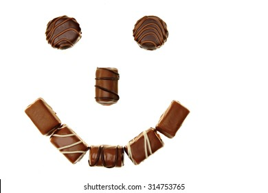 Smile from tasty chocolates candies on white background
