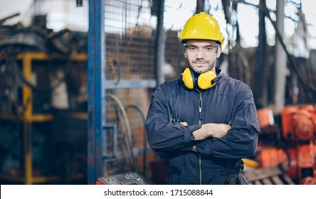 Smile technician Engineer man arms cross and hold portable radio in factory