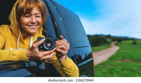 smile tourist girl in an open window of a auto car taking photography click on retro vintage photo camera, photographer looking on camera technology, blogger using hobby content concept, enjoy trip
