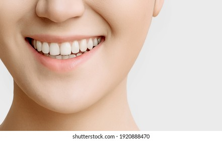 smile of a woman with beautiful white teeth close-up on a white background copy space.the concept of smooth healthy teeth