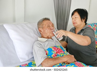 smile woman nurse assist grandfather drink water on hospital ward bed.