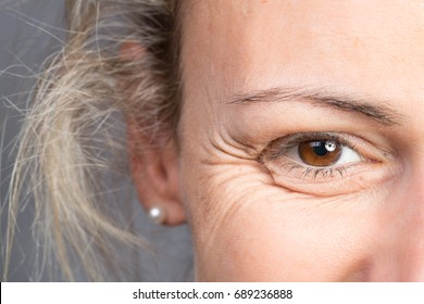 Smile of young blonde woman showing crows feet and wrinkles