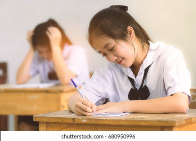 Smile young girl student reading and writing exam with not stress.