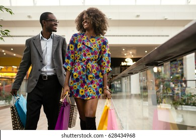 Smiled afro-american couple walking together in a shopping mall with a lot of coloured shopping bags