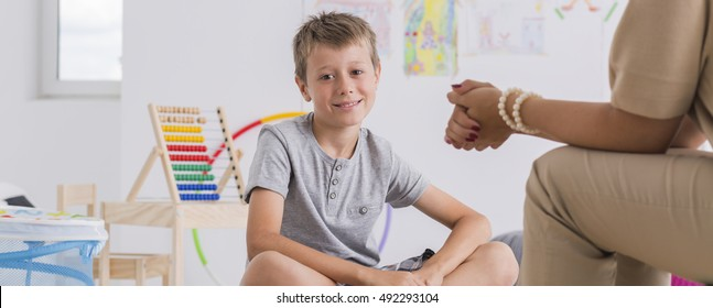 Smiled boy sitting on the floor during the psychotherapy session