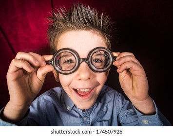 Smiled child with big glasses. Red curtain background