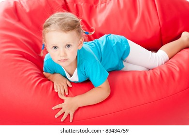 Smiled child on the red pouf chair