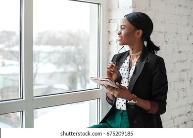 Smiled girl with dark shiny skin sitting on the windowsill, holding the tablet and looking out the window.