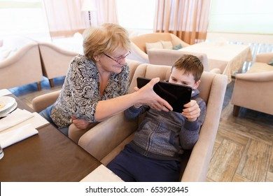 Smiled grandmother with a grand child using a tablet while eating. Cartoons and games at mealtime problem