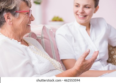 Smiled nurse listening to the story narrating by elder woman