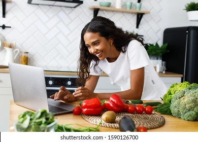 Smiled pretty girl is looking on the laptop screen  on the modern kitchen on the table full of vegetables and fruits, dressed in white t-shirt