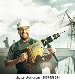Smiled workman in helmet, glasses and overalls hold perforator in his hands over the buildings. Filtered.