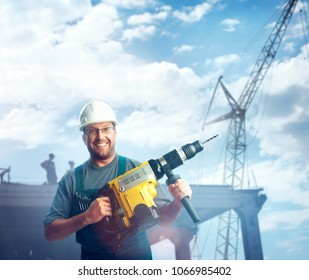 Smiled workman in helmet, glasses and overalls hold perforator in his hands over the buildings