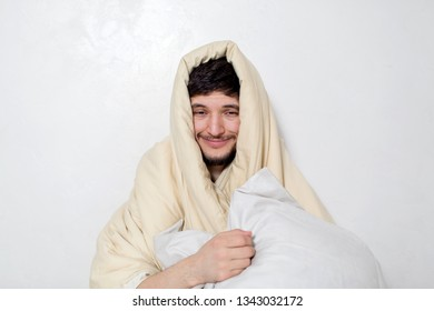 Smiles young man under the blanket. White background