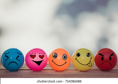 Smiley balls and Emotion balls on wooden table with bokeh wall background and copy space