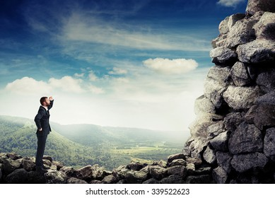smiley businessman holding his hand near brow and looking up at stone mountain