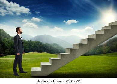 smiley businessman standing on the green meadow and looking up to the stairs